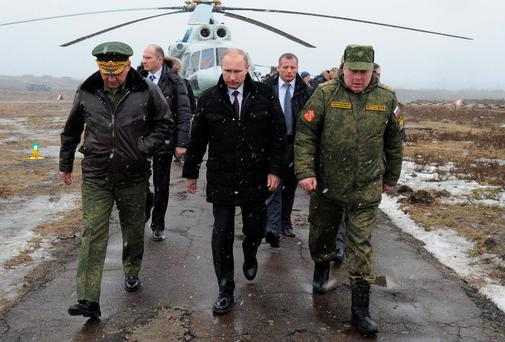 Russian President Vladimir Putin, centre, and Defence Minister Sergei Shoigu, left, and the commander of the Western Military District Anatoly Sidorov, right, arrive to watch military exercise near St.Petersburg, Russia