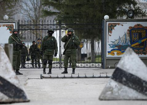 Military personnel, believed to be Russian servicemen, stand in front of the gates of a Ukrainian military unit as Ukrainian servicemen behind them look on in the village of Perevalnoye outside Simferopol. Photo: Reuters/David Mdzinarishvili