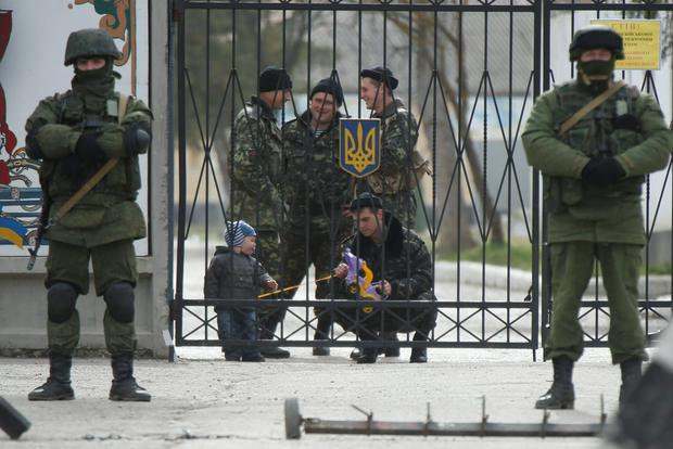 A Ukrainian serviceman plays with a child as men believed to be Russian servicemen stand in front of the gates of a Ukrainian military unit in the village of Perevalnoye outside Simferopol. President Vladimir Putin has ordered troops that took part in military exercises in central and western Russia to return to base after completing their training. Photo: Reuters/David Mdzinarishvili