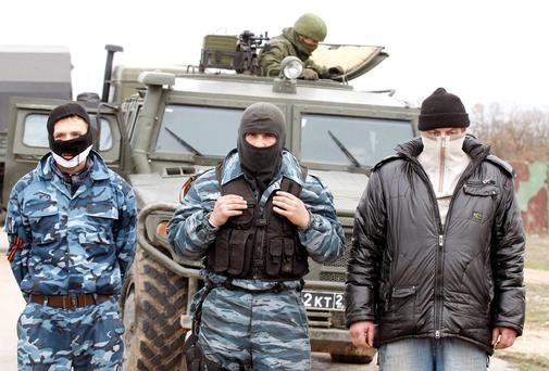 A Russian serviceman is seen on a vehicle behind pro-Russian activists at the Belbek Sevastopol International Airport in the Crimea region