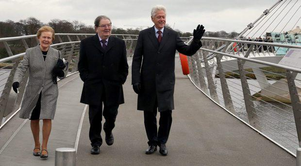 Former US President Bill Clinton with John Hume and his wife Pat as they walk along Peace Bridge in Derry city