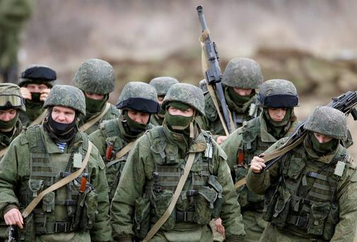 Uniformed men, believed to be Russian servicemen, march outside a Ukrainian military base in the village of Perevalnoye