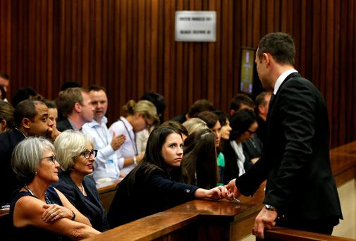 Aimee Pistorius, sister of Olympic and Paralympic track star Oscar Pistorius, holds his hand ahead of his trial for the murder of his girlfriend Reeva Steenkamp