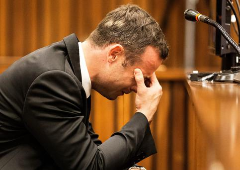 Oscar Pistorius, puts his hand to his face while listening to evidence from a witness speaking about the morning of the shooting