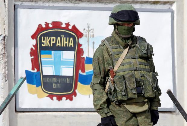 A uniformed man, believed to be a Russian serviceman, stands guard near a Ukrainian military base in the village of Perevalnoye, outside Simferopol