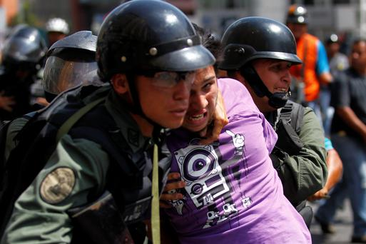 National guards detain a protester during riots in Caracas