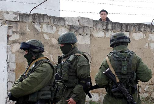 A Ukrainian serviceman (rear) looks at uniformed men, believed to be Russian servicemen, standing guard at a Ukrainian military base in the village of Perevalnoye, outside Simferopol