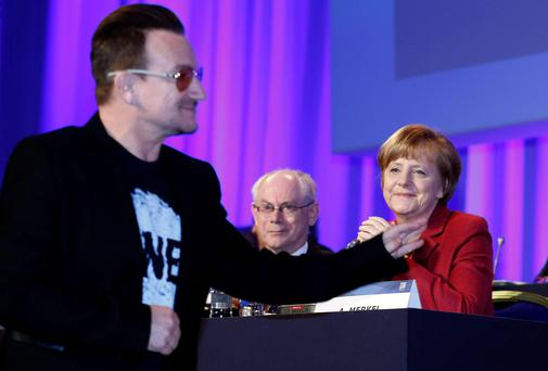 German Chancellor Angela Merkel (R) and European Council President Herman Van Rompuy look on as Bono arrives at the European People's Party (EPP) Elections Congress in Dublin March 7, 2014. REUTERS/Suzanne Plunkett