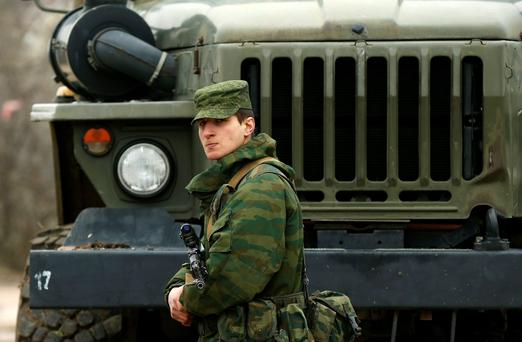 A uniformed man, believed to be a Russian serviceman, stands guard near a Ukrainian military base outside the city of Sevastopol REUTERS/David Mdzinarishvili