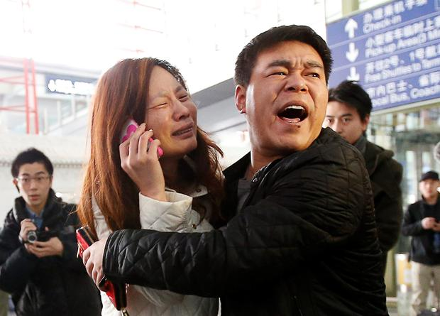 A relative (woman in white) of a passenger onboard Malaysia Airlines flight MH370 cries as she talks on her mobile phone at the Beijing Capital International Airport March 8, 2014. TREUTERS/Kim Kyung-Hoon