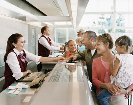 Passengers at airport check-in desk. Photo: Getty Images.
