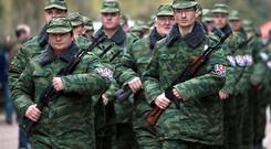 Armed members of the first unit of a pro-Russian armed force, dubbed the 'military forces of the autonomous republic of Crimea' march before the swearing-in ceremony in Simferopol, Ukraine. Some 30 men armed with automatic weapons and another 20 or so unarmed, were sworn in at a park in front of an eternal flame to those killed in World War II. AP