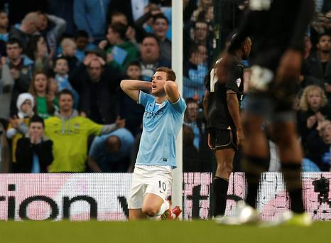 Manchester City's Edin Dzeko reacts after a missed opportunity during their English FA Cup quarter final defeat to Wigan