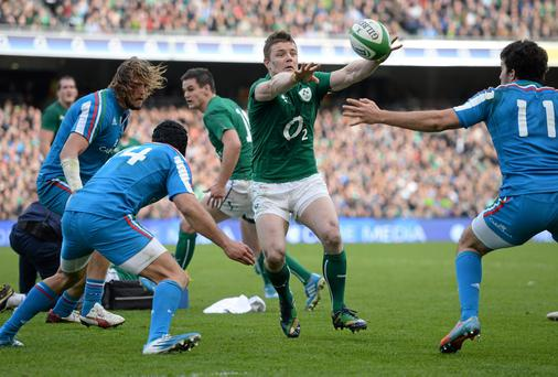 Brian O'Driscoll, Ireland, slips a pass through Angelo Esposito, left, and Leonardo Sarto, Italy, to Andrew Trimble