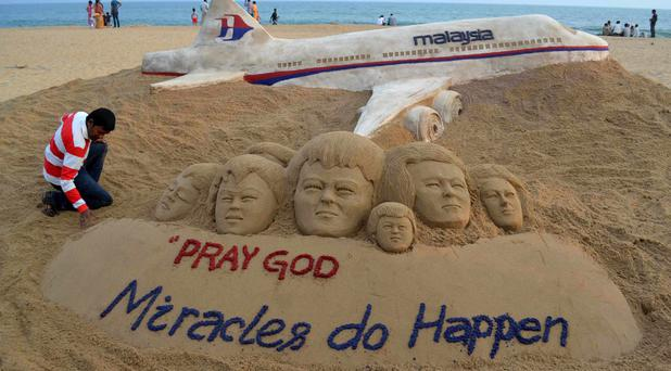 Indian sand artist Sudarshan Patnaik applies the final touches to a sand art sculpture he created wishing for the well being of the passengers of Malaysian Airlines flight MH370, on a beach in Puri, in the eastern Indian state of Odisha,