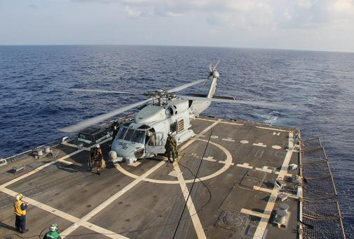 A U.S. Navy MH-60R Sea Hawk helicopter lands aboard Pinckney before returning on task in the search and rescue for the missing Malaysian airlines flight MH37