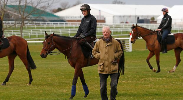Ruby Walsh on Hurricane Fly walk behind trainer Willie Mullins after a workout on the gallops at the Cheltenham racecourse