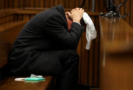 Olympic and Paralympic track star Oscar Pistorius holds his head in his hands, in the dock during his trial for the murder of his girlfriend Reeva Steenkamp