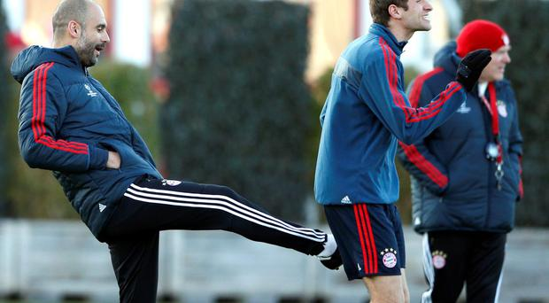 Bayern head coach Pep Guardiola of Spain, jokes with Thomas Mueller, during a training session