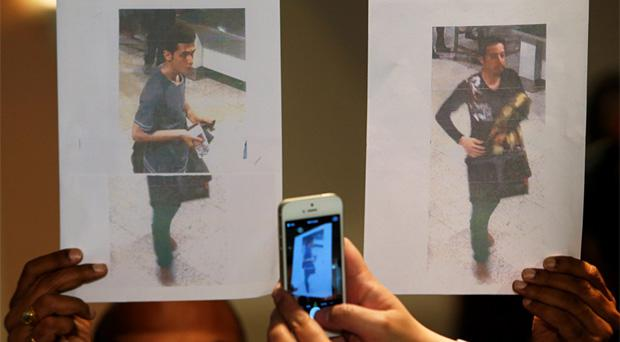 A policeman holds up photos of the two men whom they believe were travelling onboard the missing Malaysia Airlines flight on stolen passports