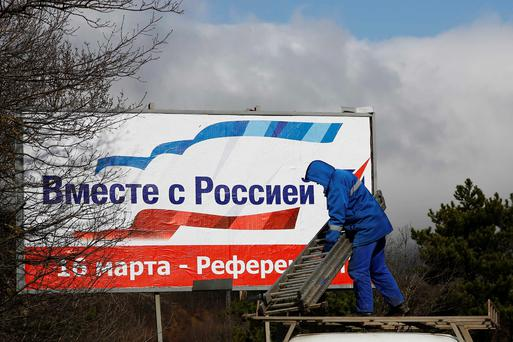 A man puts up a poster calling on Crimea residents to vote in favour of the Ukrainian peninsular joining the Russian federation, at a highway outside of Simferopol March 11, 2014. The poster reads,