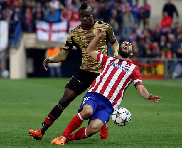 AC Milan's Mario Balotelli (L) challenges Atletico Madrid's Arda Turan during their Champions League last 16 second leg soccer match at Vicente Calderon stadium in Madrid March 11, 2014. REUTERS/Juan Medina