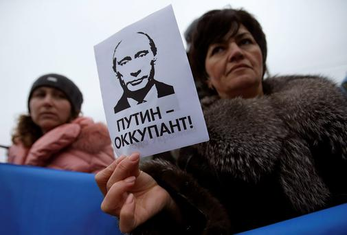 A woman holds a sign with a portrait of Russian President Vladimir Putin and the words