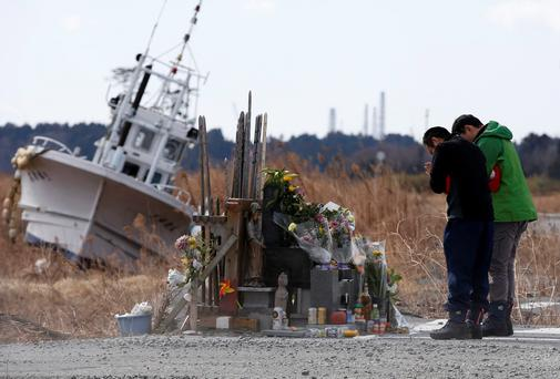 People pray for victims of the March 11, 2011 earthquake and tsunami as Tokyo Electric Power Co's (TEPCO) tsunami-crippled Fukushima Daiichi nuclear power plant is seen in the background at Namie town, Fukushima prefecture