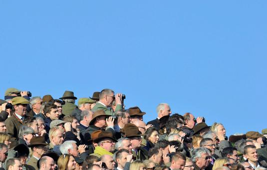 Racegoers watch on the first day of the Cheltenham Festival horse racing meet in Gloucestershire, England. The four-day festival is a highlight of the annual jump racing calendar. Reuters