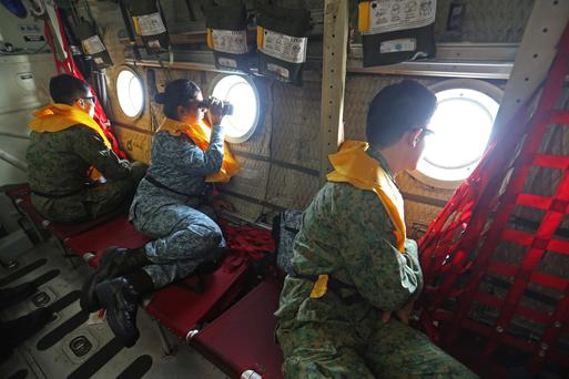 Military personnel look out of a Republic of Singapore Air Force (RSAF) C130 transport plane as they search for the missing Malaysia Airlines MH370 plane. Photo: Reuters/Thong Kah Hoong Dennis/Lianhe Zaobao/Singapore Press Holdings Ltd