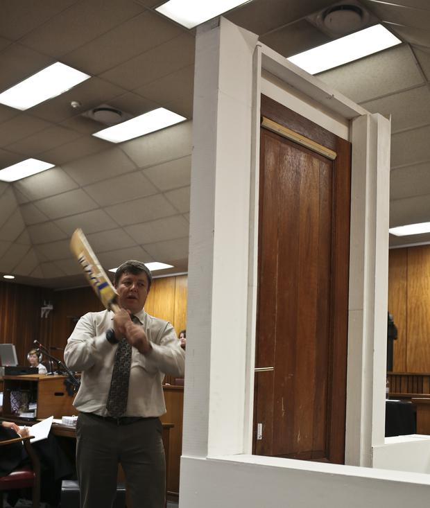 A policeman takes part in the reconstruction of the hitting of the door with the cricket bat during the trial of South African Paralympic athlete Oscar Pistorius at the North Gauteng High Court in Pretoria on March 12, 2014. Oscar Pistorius's murder trial was set to hear more details on the autopsy of his slain girlfriend Reeva Steenkamp, a day after the star sprinter threw up as he listened to a graphic account of the gunshot injuries he inflicted on his lover. AFP PHOTO / POOL / ALEXANDER JOE (Photo credit should read ALEXANDER JOE/AFP/Getty Images)