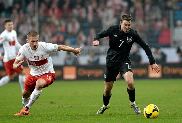 Aiden McGeady, Republic of Ireland, in action against Piotr Celeban, Poland