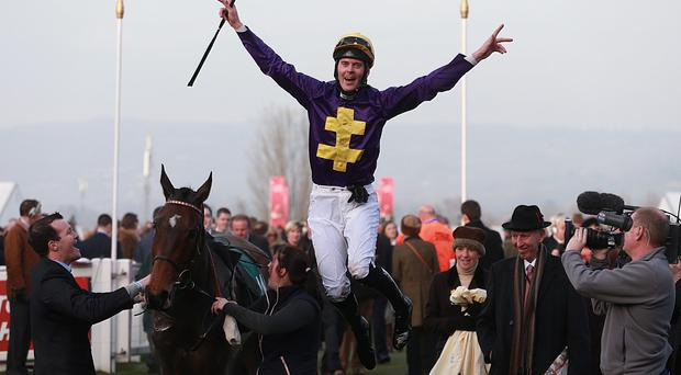 Robbie McNamara jumps off Spring Heeled as he celebrates winning the Fulke Walwyn Kim Muir Challenge Cup Handicap Chase during St Patrick's Day at Cheltenham Racecourse, Cheltenham. PRESS ASSOCIATION Photo. Picture date: Thursday March 13, 2014. See PA story RACING Cheltenham. Photo credit should read: David Davies/PA Wire