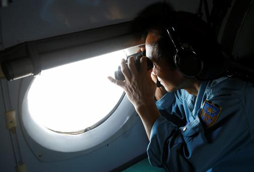 Military officer Pham Tuan Minh looks through a window of a Vietnam Air Force AN-26 aircraft during a mission to find the missing Malaysia Airlines flight MH370