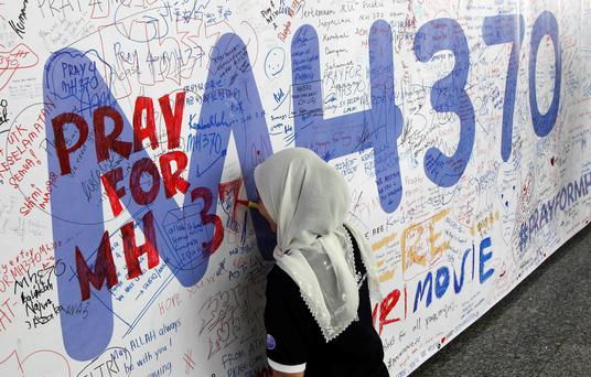 A woman writes on a banner of well wishes for the passengers of the missing Malaysia Airlines Flight MH370 at Kuala Lumpur International Airport March 14, 2014.
