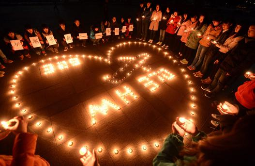 College students light up candles as they pray for passengers of the missing Malaysia Airlines MH370 plane in Yangzhou, Jiangsu province, China. Photo: Reuters/Stringer