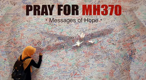 A woman writes a message for passengers aboard a missing Malaysia Airlines plane, at a shopping mall in Kuala Lumpur, Malaysia, Saturday, March 15, 2014. Investigators have concluded that one or more people with significant flying experience hijacked the missing Malaysia Airlines jet, switched off communication devices and steered it off-course, a Malaysian government official involved in the investigation said Saturday. (AP Photo/Lai Seng Sin)