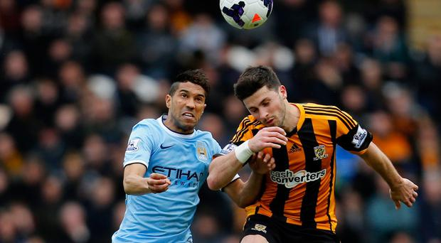 Manchester City's Gael Clichy competes for a header with Shane Long of Hull City during the Barclays Premier League match between the two sides