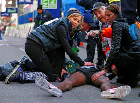 Mo Farah of Great Britain is taken care of by medical personal after he collapsed at the finish line after finishing in second place at the 2014 New York City Half Marathon in lower Manhattan.