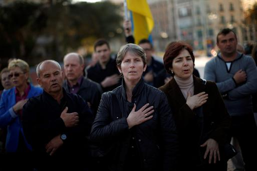Ukrainians living in Malaga sing the Ukrainian anthem during a protest against Russian President Vladimir Putin and in favor of unity and democratic freedom in Ukraine, in downtown Malaga, southern Spain