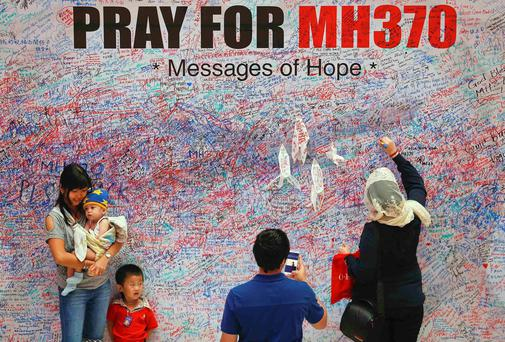 A woman leaves a messages of support and hope for the passengers of the missing Malaysia Airlines MH370