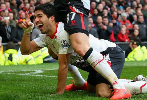 Luis Suarez of Liverpool celebrates scoring his team's third goal with Martin Skrtel