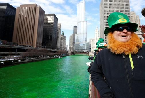 A man dressed as a leprechaun smiles as he stands beside the dyed green Chicago River during St. Patrick's Day celebrations in Chicago