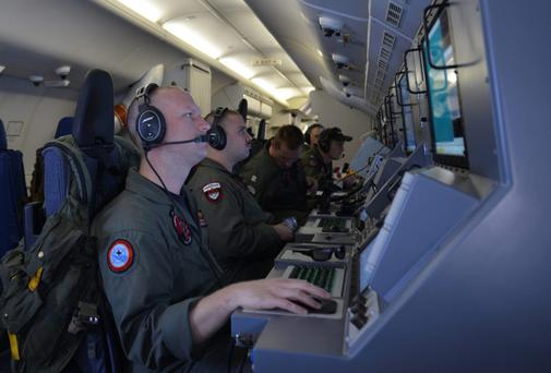 Crew members on board a U.S. Navy P-8A Poseidon man their workstations while assisting in search operations for Malaysia Airlines flight MH370