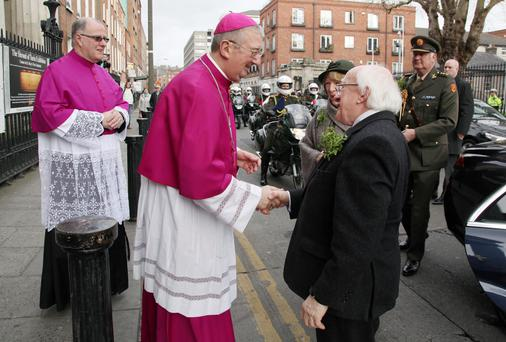 Archbishop of Dublin Diarmuid Martin greets President Michael D Higgins at the Pro Cathedral in Dublin for St Patrick's Day yesterday. Photo: JOHN McELROY