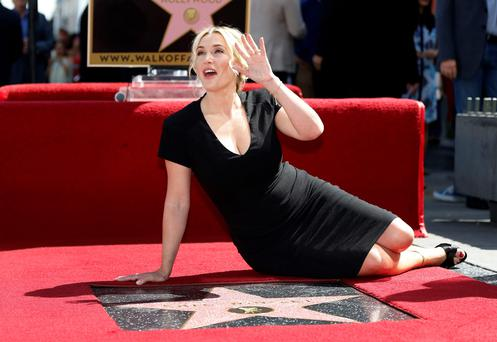Actress Kate Winslet poses on her star after it was unveiled on the Walk of Fame in Hollywood, California March 17, 2014. REUTERS/Mario Anzuoni