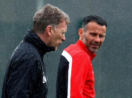 Manchester United's manager David Moyes (L) walks past Ryan Giggs during a training session at the club's Carrington training complex in Manchester, northern England March 18, 2014