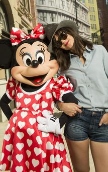 LAKE BUENA VISTA, FL - MARCH 16: In this handout photo provided by Disney Parks, Katie Holmes poses with Minnie Mouse in the New York Street area of Disney's Hollywood Studios on March 16, 2014 at Walt Disney World Resort in Lake Buena Vista, Florida. (Photo by David Roark/Disney Parks via Getty Images)