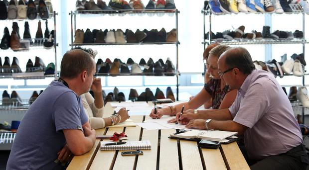 Employees make notes during a meeting at Asos headquarters in London