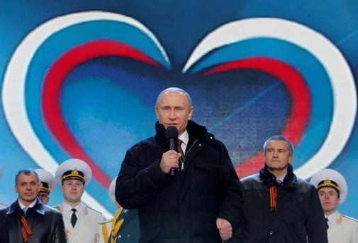 Russia's President Vladimir Putin (front) addresses the audience during a rally and concert called 'We are together' to support the annexation of Ukraine's Crimea to Russia, with Crimea's Prime Minister Sergei Aksyonov and parliamentary speaker Vladimir Konstantinov (L) seen in the background, at the Red Square in central Moscow. Photo: Reuters